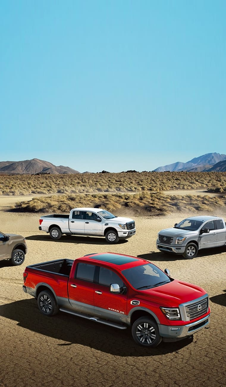 Multiple Nissan pick-up trucks are parked on a desert terrain.