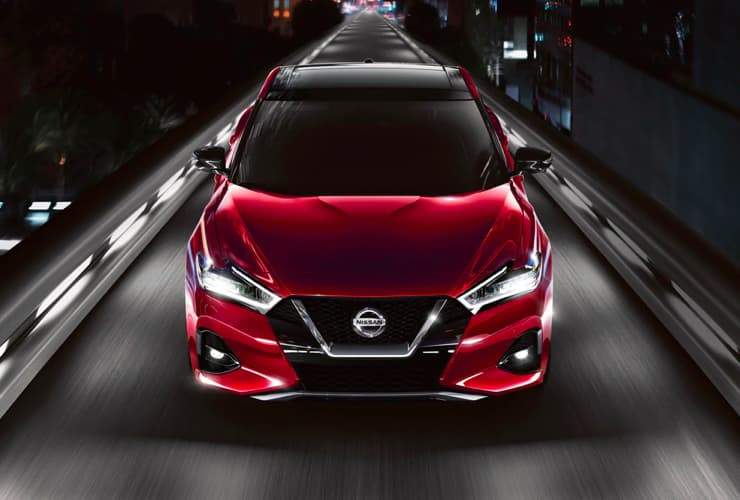 A front facing red Nissan car