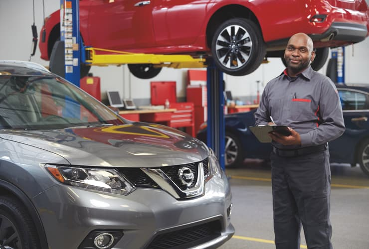 A service technician beside a Nissan car