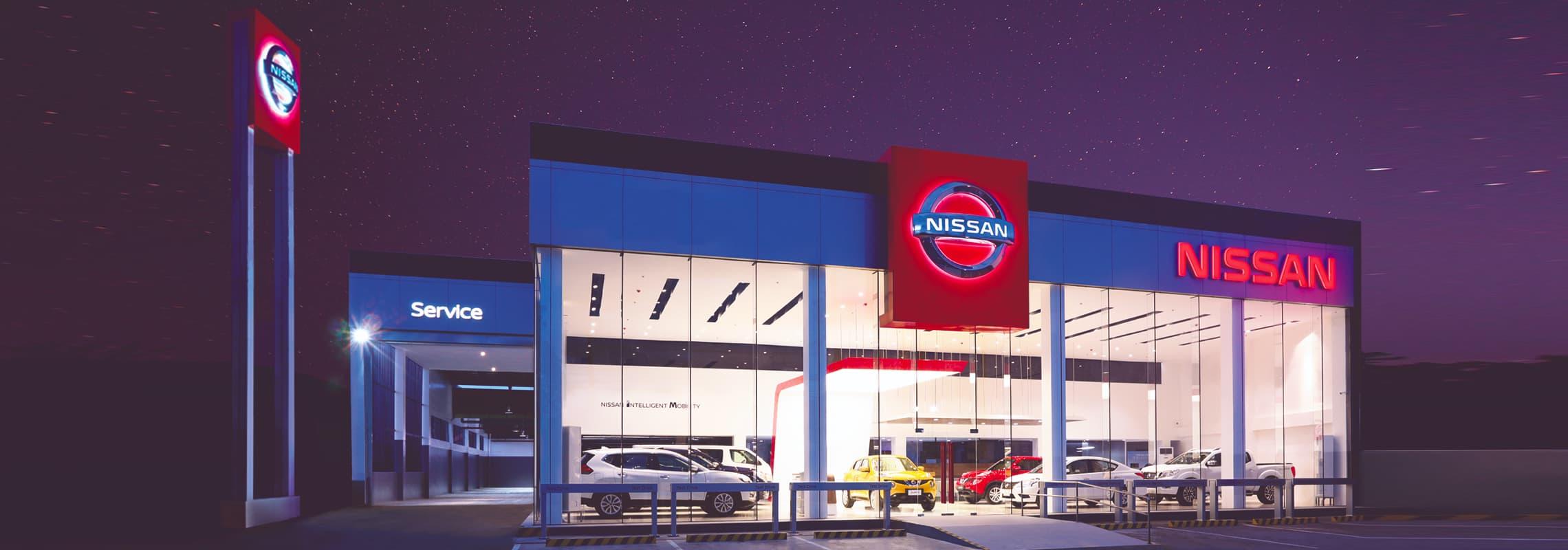 An exterior shot of a Nissan dealership at night