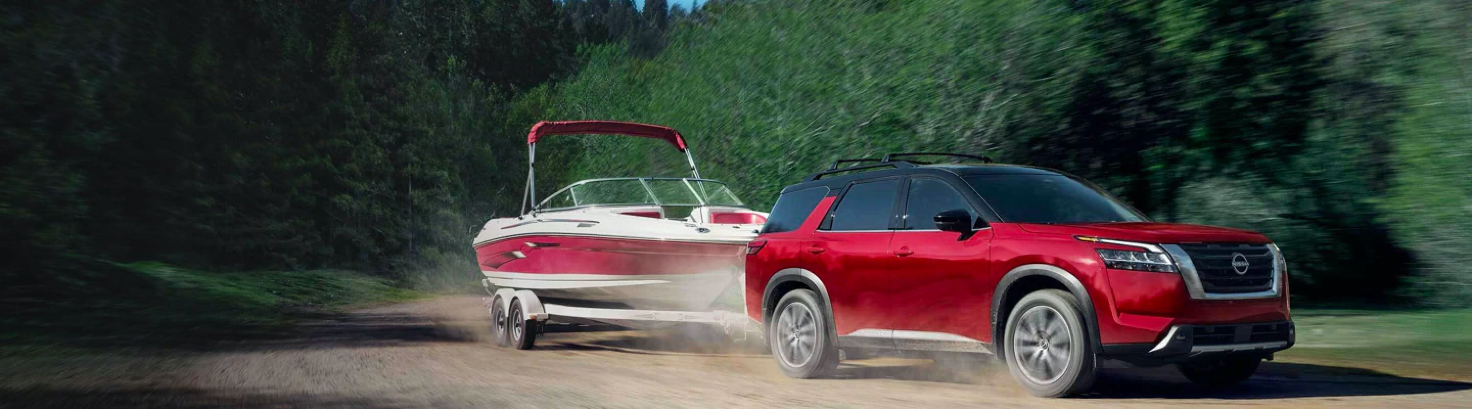 2022 Nissan Pathfinder towing a boat on a dirt road