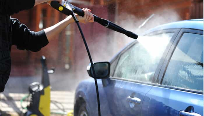 Person with hose spraying car window